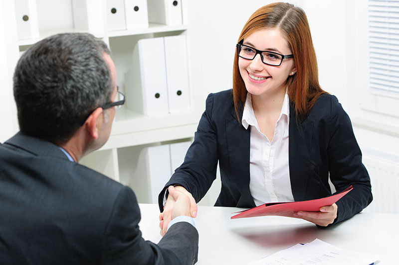 woman shaking hands with male sitting at desk