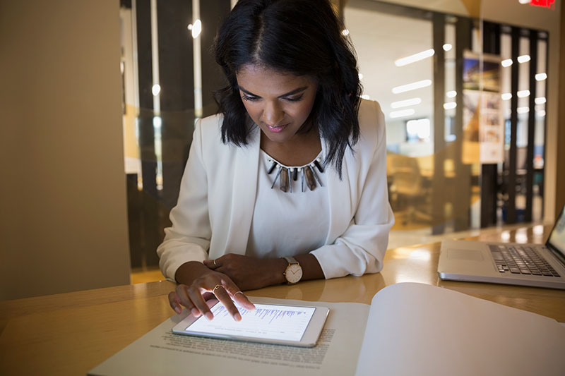 woman using digital tablet sitting at desk